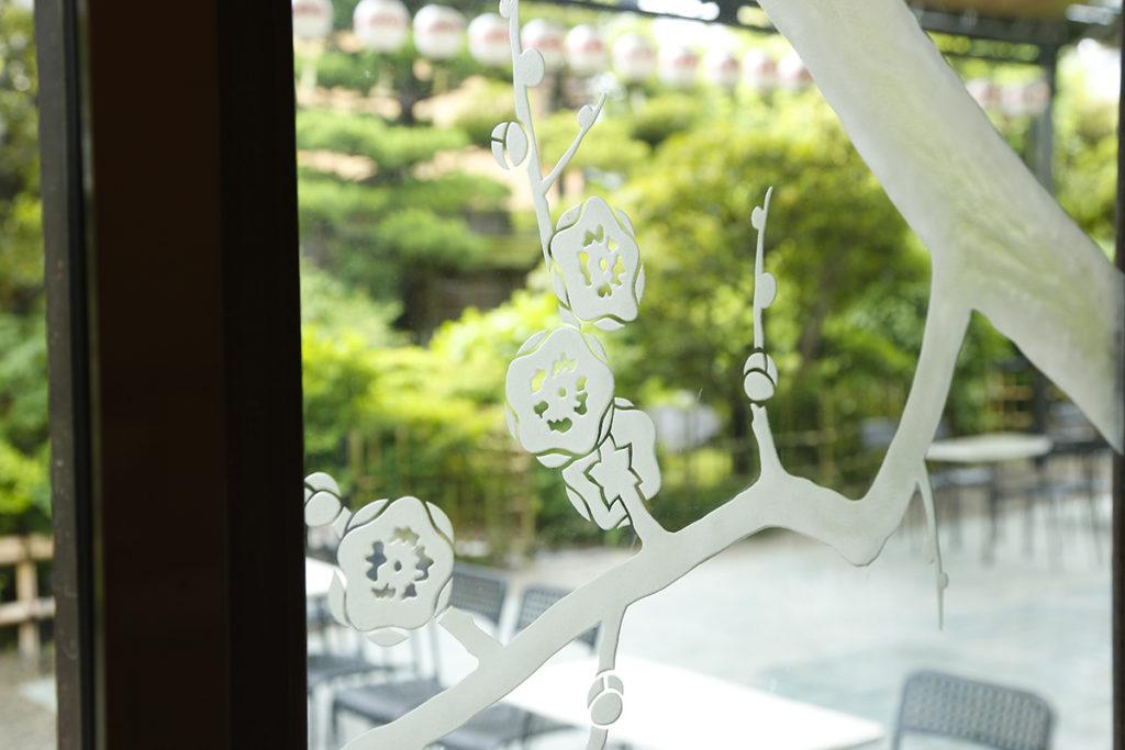 梅のグラビュールを施した窓ガラスから前庭を望む